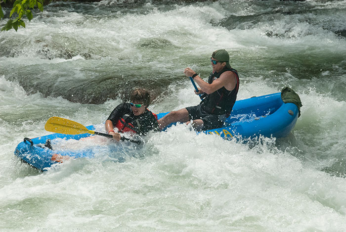 negotiating rapids in a 'ducky' kayak
