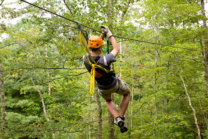 man riding a zipline in the Nantahala Gorge