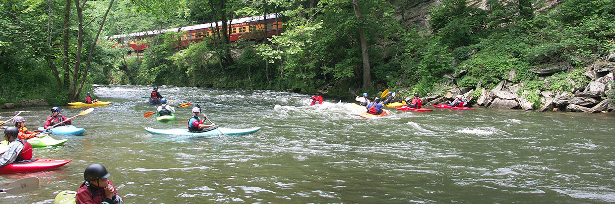 Kayakers on the Nantahala with scenic railroad in background